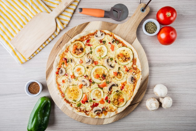 Vegane pizza mit zucchini, champignons, tomaten, paprika und oregano