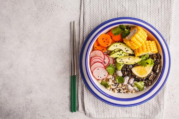Vegane poke bowl mit naturreis, grünkohl und gemüse.