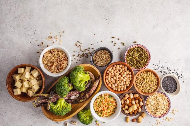 Vegane proteinquelle. tofu, bohnen, kichererbsen, nüsse und samen auf einem weißen hintergrund, draufsicht, kopienraum.