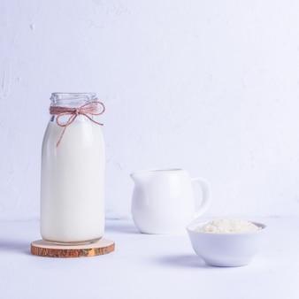 Vegane reismilch in einer glasflasche und reis in einer weißen platte auf einem holzständer auf einem weißen hintergrund