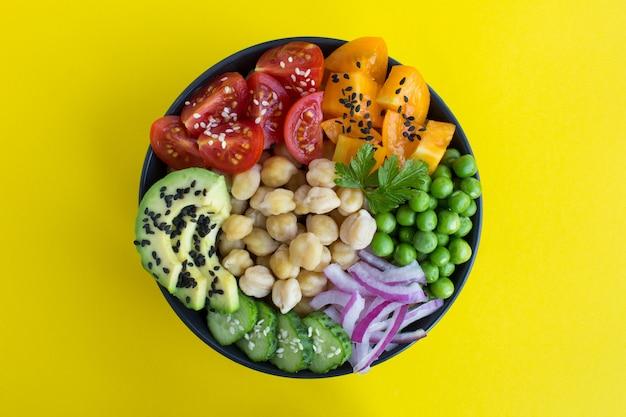 Vegane sackschale mit kichererbsen und gemüse in der schwarzen schüssel in der mitte des gelben hintergrunds. draufsicht.