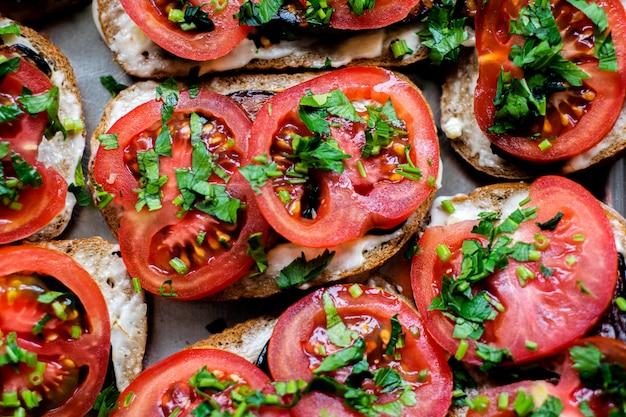 Vegane sandwiches mit köstlichen toasts und frischem gemüse, einschließlich geschnittener tomaten