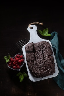 Vegane schokoladen-brownie-torte mit tahini und frischen himbeeren auf dunklem hintergrund