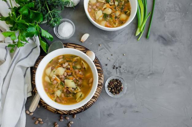 Vegane suppe mit bohnen und nudeln in einer schüssel auf einem brett auf einem dunklen betonhintergrund. horizontale ausrichtung.