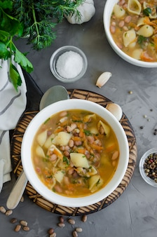 Vegane suppe mit bohnen und nudeln in einer schüssel auf einem brett auf einem dunklen betonhintergrund.
