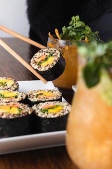 Vegane sushi-rollen mit quinoa, gemüse und sojasauce