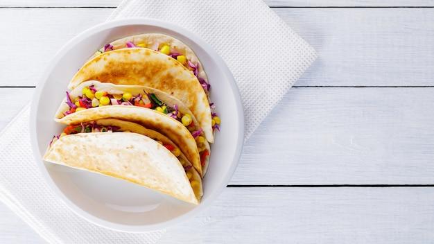 Vegane tacos mit mais, purpurkohl und tomaten auf einem weißen teller. mexikanische tacos mit verschiedenem gemüse auf weißen tafeln. gesundes essen. mexikanische küche