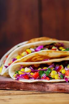 Vegane tacos mit verschiedenem gemüse auf einem schneidebrett. tacos mit zuckermais, purpurkohl und tomaten auf holzbrettern. platz kopieren