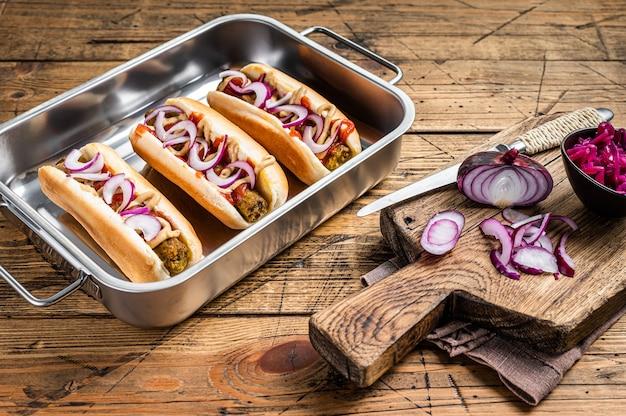 Vegane vegetarische hot-dogs mit zwiebeln und fleischloser wurst. hölzerner hintergrund. ansicht von oben.