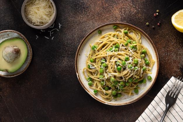 Vegane vollkornnudeln mit grünen erbsen und italienischem avocado-essen