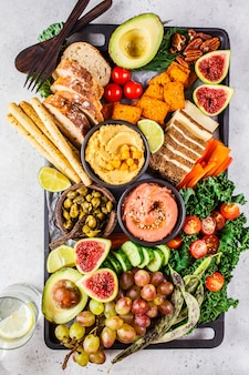 Vegane vorspeisenplatte, hummus, tofu, gemüse, obst und brot