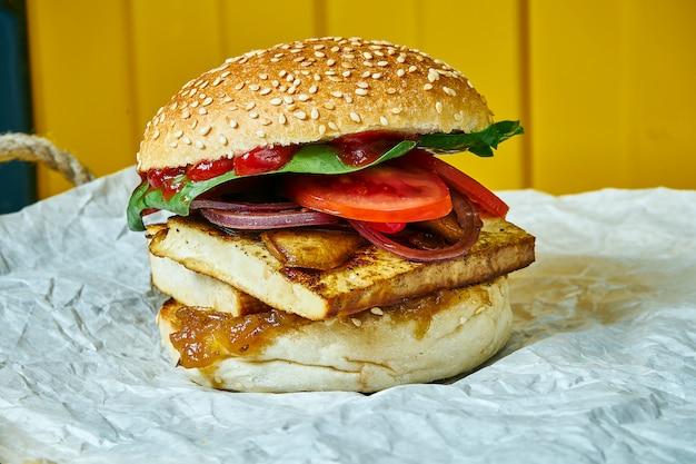 Veganer burger mit gemüse, spinatpilzen, tomaten und tofukäse auf bastelpapier auf einem gelben tisch. gesundes fast food