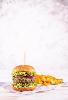 Veganer burger mit kartoffelecken auf einem weißen tisch