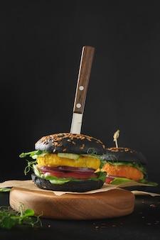 Veganer burger von schwarzen holzkohlebrötchengemüse-fleischbällchen auf schwarz