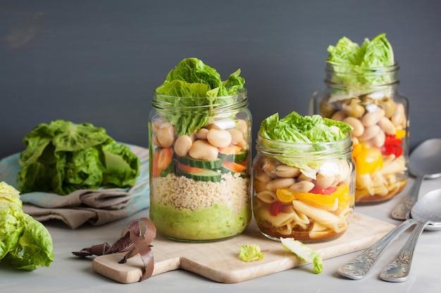 Veganer couscous- und nudelsalat in einmachgläsern mit gemüsebohnen