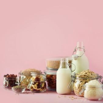 Veganer ersatzmilchmilch. glasflaschen mit nichtmilchmilch und bestandteilen über rosa hintergrund mit kopienraum.