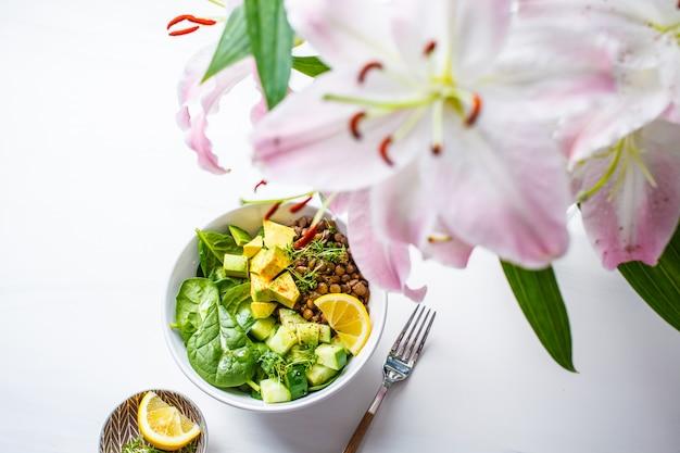 Veganer flachsalat mit spinat, linsen, avocado und gurke.