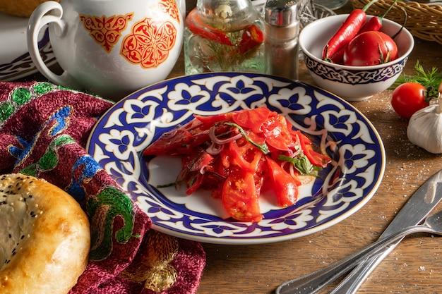 Veganer gemüsesalat acecook saftige tomaten mit süßen zwiebeln in einer schüssel mit traditionellem usbekischem muster.