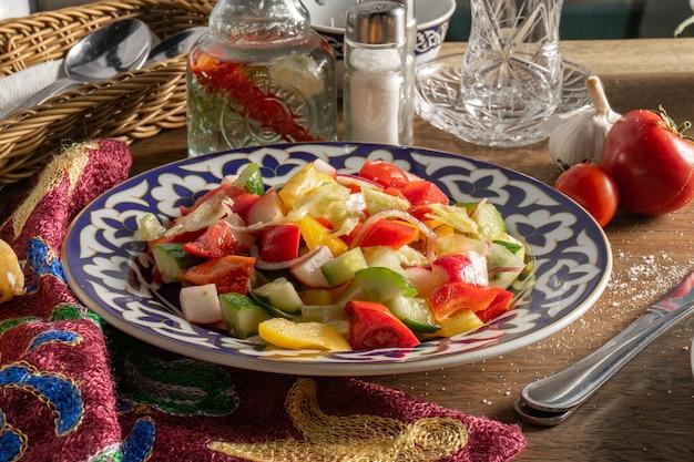 Veganer gemüsesalat aus paprika, gurken, tomaten, radieschen und zwiebeln in einer keramikplatte mit traditionellen usbekischen ornamenten auf einem holztisch neben besteck mit gabel und messer.
