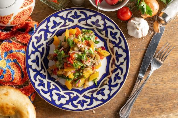 Veganer gemüsesalat aus tomaten, gurken, radieschen, paprika, roten zwiebeln und salatblättern in einem teller mit einem traditionellen usbekischen muster