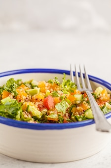 Veganer gesunder regenbogensalat mit quinoa, tofu, avocado und kohl.