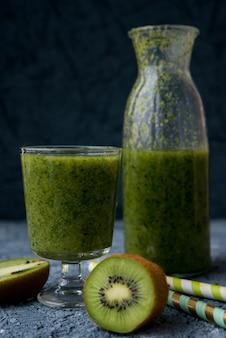 Veganer grüner smoothie in einer flasche kiwi, spinat und banane