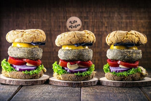 Veganer hamburger mit hamburger auf sojabasis. holzschild geschrieben in englisch life vegan