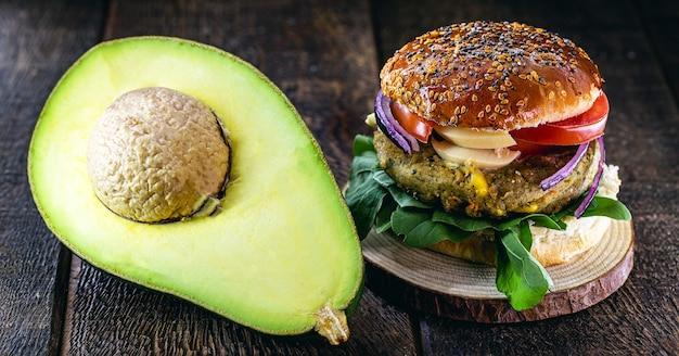 Veganer hamburger ohne fleisch, snack auf avocado-basis. vegetarisches sandwich mit rustikaler kartoffel