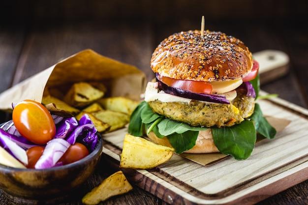 Veganer hamburger, ohne fleisch, snack auf basis von samen, soja, pflanzen und eiweiß. vegetarisches sandwich mit rustikaler kartoffel