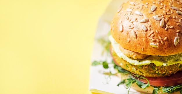 Veganer hausgemachter burger mit glutenfreiem brötchen und schnitzel auf gemüsebasis