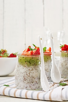 Veganer kokosmilch-chiasamen-pudding mit erdbeeren und kiwi.