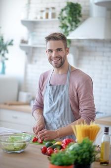 Veganer lebensstil. ein junger mann, der gemüse für einen salat hackt