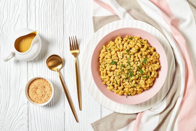 Veganer mac und käse mit nährhefesauce in einer rosa schüssel auf einem weißen holztisch mit goldenem besteck, landschaftsansicht von oben, nahaufnahme, flacher lay