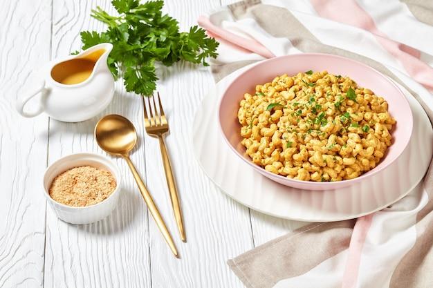 Veganer mac und käse mit nährhefesauce in einer rosa schüssel auf einem weißen holztisch mit goldenem besteck, landschaftsansicht von oben, nahaufnahme
