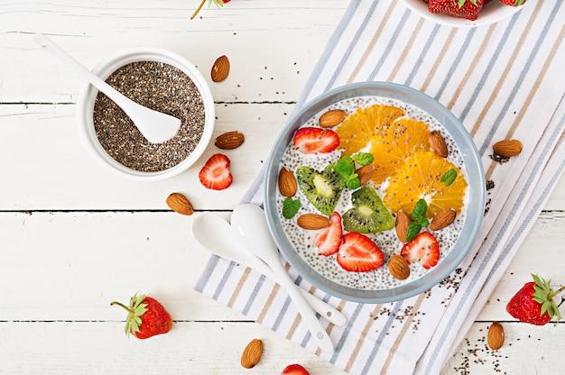 Veganer mandelmilch-chiasamen-pudding mit erdbeeren, orange und kiwi.