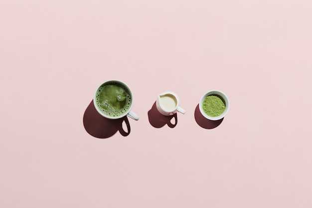 Veganer matcha latte mit hafermilch und zutaten auf pink
