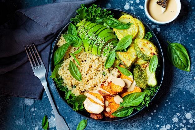 Veganer mittagsteller. quinoa-salat mit gebackener zucchini, süßkartoffel, avocado und tahini-dressing auf schwarzem teller