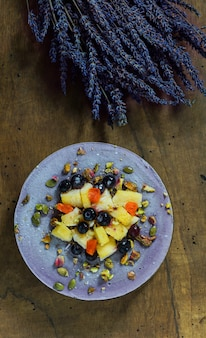 Veganer rohkäsekuchen mit heidelbeere, kirsche, matchatee, orange, cashewcreme, kokosnussbutter und kokosmilch sowie basis aus mandeln, datteln und getrockneten aprikosen, haferflocken, lyophilisierten beeren