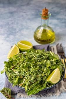 Veganer salat aus grünen salatblättern und mikrogrün mit limette auf einem teller