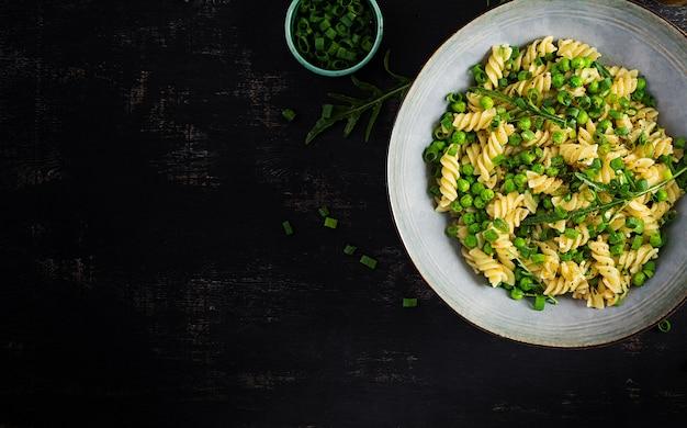 Veganer salat. fusilli-nudeln mit erbsen und zwiebeln. italienisches essen. draufsicht. flach liegen.