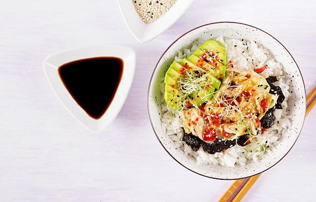 Veganer salat mit reis, eingelegtem kimchi-kohl, avocado, nori und sesam auf schüssel