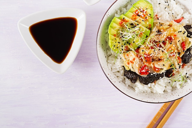Veganer salat mit reis, eingelegtem kimchi-kohl, avocado, nori und sesam auf schüssel.