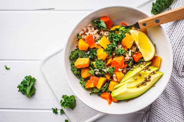 Veganer salat mit reis, grünkohl, gebackenem kürbis, karotten und avocado