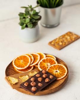 Veganer schokoladen-milchschokoladen-holzteller mit schokolade und trockenfrüchten