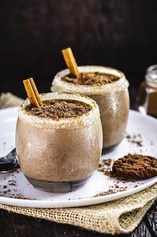Veganer schokoladenpudding kalt serviert, mit mandelmilch