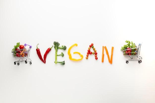 Veganer schriftzug aus gemüse mit winzigen einkaufswagen