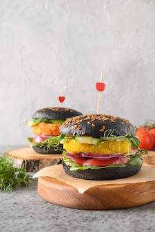Veganer schwarzer burger von gemüsekohl und karottenfleischbällchen als fleisch auf pflanzlicher basis