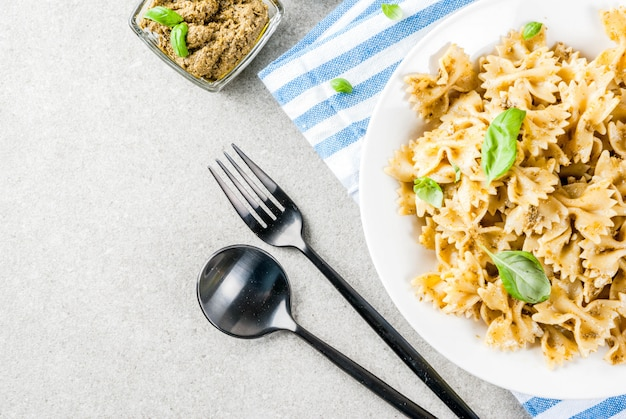 Veganes abendessen. farfalle-nudeln mit pesto-sauce und basilikumblättern