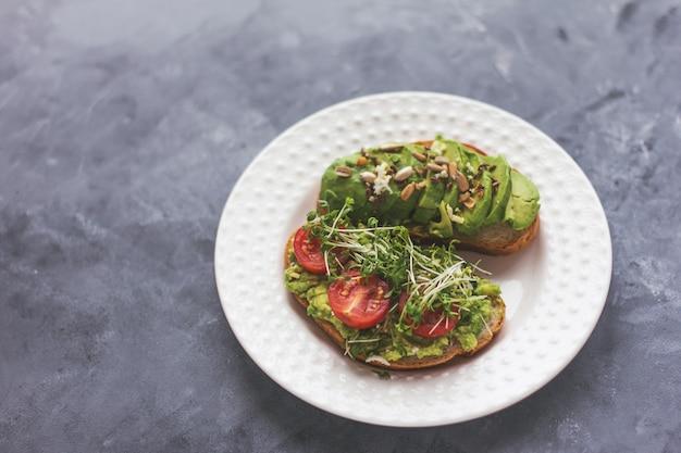 Veganes avocado-sandwich mit microgreens auf einem weißen teller auf einer grauen oberfläche