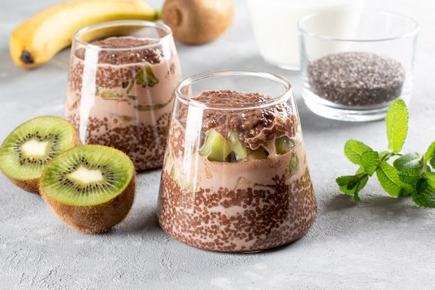 Veganes dessert, chia pudding mit kiwi und banane auf grauem tisch